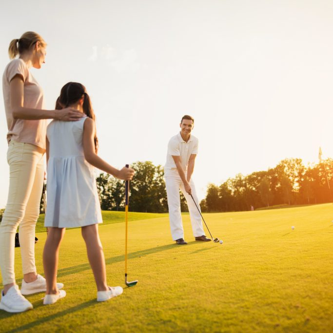 A woman and a girl are standing with golf clubs in their hands and looking at a man in a white suit who is preparing to hit the golf club with the ball.